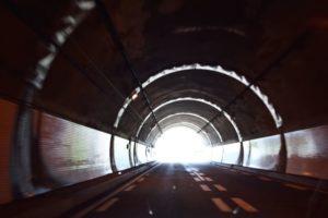 暗いトンネルの中から明るい出口が見え希望が見える
