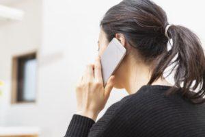 派遣の仕事を辞めたいので派遣会社に相談の電話をする女性